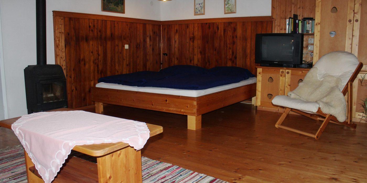Wohnzimmer mit Doppelbett, Fernseher und Ofen